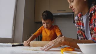 Child helping mother rolling out dough for cookies