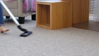 Close-up of female hoovering carpet