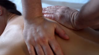Close-up of hands massaging the back and shoulder of client