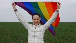 Close-up of woman with waving LGBT flag in the field