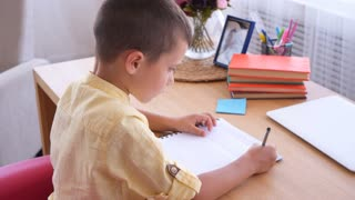 Concentrated boy writing letters in notebook