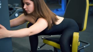 Concentrated girl exercising at hip abductor machine