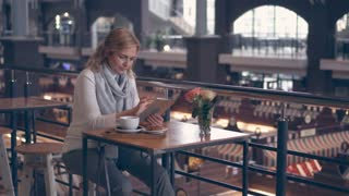 Concentrated mature woman working on tablet in cafe