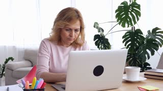Concentrated middle-aged woman working on laptop