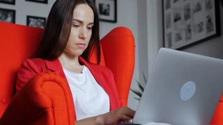 Concentrated woman sits in armchair with laptop