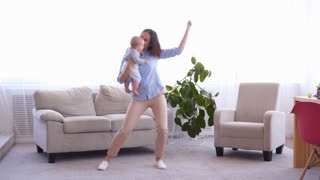 Cool mother dancing with baby girl in living room
