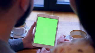 Couple using tablet with green screen during coffee break