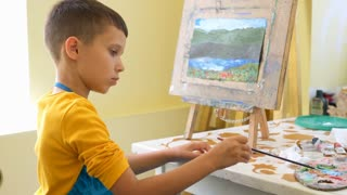 Creative boy painting on easel