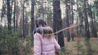 Curious girl in pink coat looking around while walking in forest