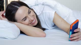 Delightful female lying on the pillow and using mobile phone