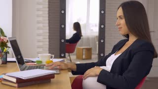 Delightful pregnant businesswoman drinking tea while working on laptop