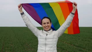 Delightful woman raised arms with LGBT flag