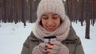 Delightful young woman in a warm outfit blowing on hot beverage to cool it down