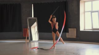 Determined girl performing vertical leg split with ribbon