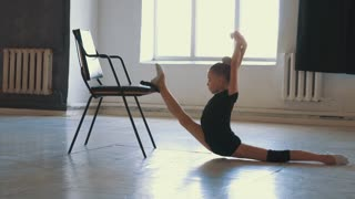 Determined gymnast doing split to stretch before class