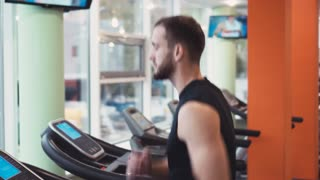 Determined young man running on treadmill