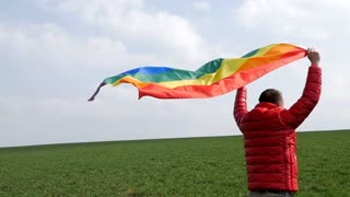 Dolly of man jumping with waving LGBT flag
