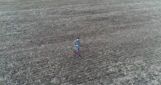 Drone footage of female in a warm clothes taking a walk in a grey spring field