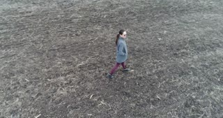 Drone is spinning around the female in sunglasses wandering the grey field