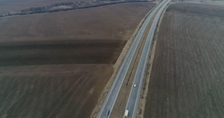 Drone shot of car driving on a highway on a dull day