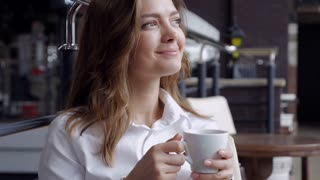 Elated brunette with a cup of coffee looking somewhere