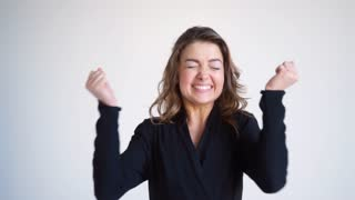 Excited brunette outstretching hands while celebrating victory