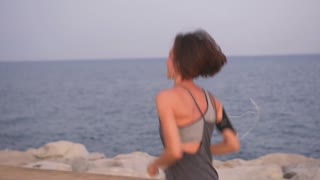 Excited fit woman jogging and dancing along beach