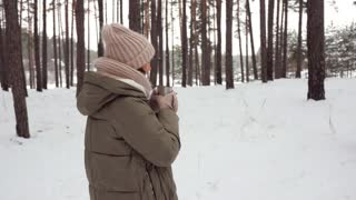 Exhilarated woman getting warm with tea on a cold day in the forest