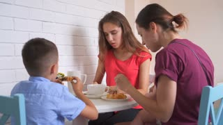 Family eating breakfast in kitchen together