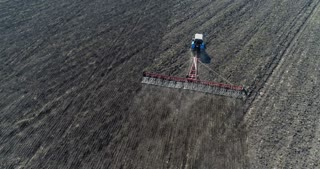 Farmer tractor seeding crops in field, aerial view