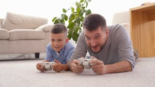 Father and son playing video games on the floor