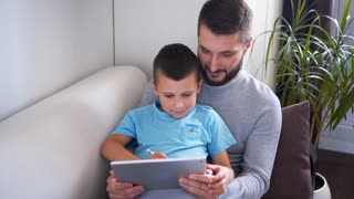 Father watching son drawing on digital tablet with pencil