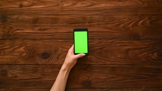 Female hands using mobile phone with white green screen