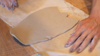 Female hands working with clay angel