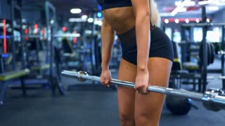 Fit girl performing barbell bent over row