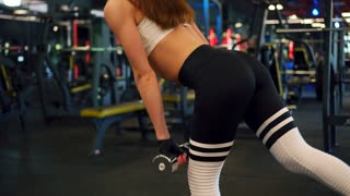 Fit girl performing bent over row with dumbbells
