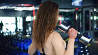 Fit girl working out with dumbbells