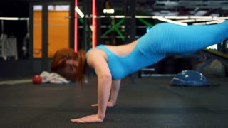 Fit redhead girl doing push-ups at gym