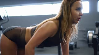 Fitness girl performing one arm bent-over dumbbell row