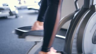 Focus on legs working out on elliptical trainer