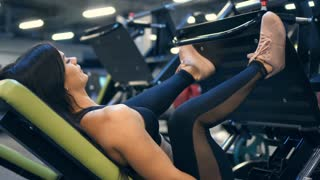 Focused sportswoman working out on leg press machine