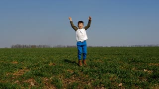 Funny small boy jumping in green field