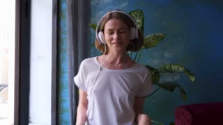 Girl dancing while listening music in headphones