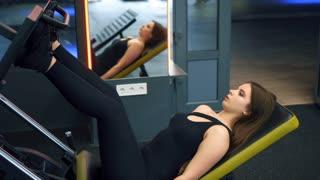 Girl flexing legs muscles using press machine