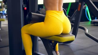 Girl flexing muscles on gym machine