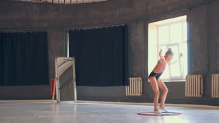 Girl in sparkling leotard exercising with hula hoop
