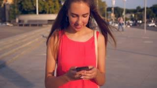 Girl walking down street using smartphone