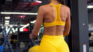 Girl with dreads improving back at gym