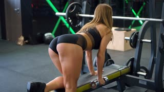 Girl working out one arm bent-over dumbbell row