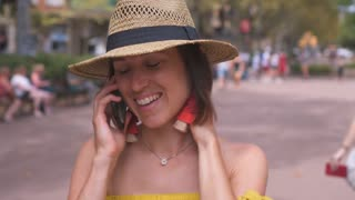 Gorgeous woman in summer outfit talking on phone in street